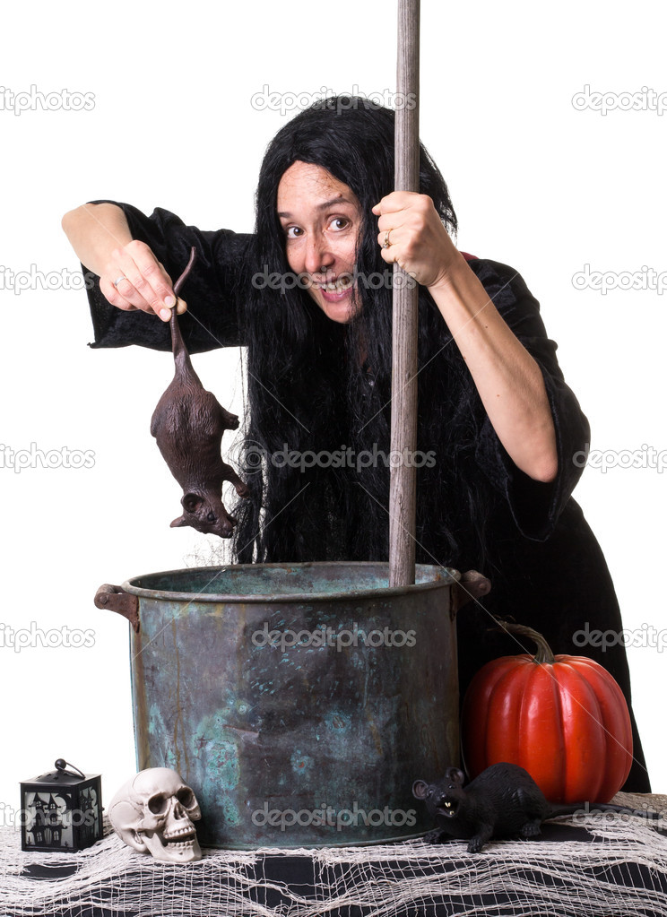 A woman in witch costume cooks up a potion for Halloween. — Stock Photo #13187523