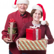 Happy Senior couple bearing gifts at Christmas — Stock Photo #13382418