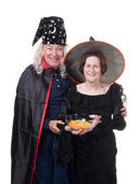Senior Couple handing out candy at Halloween — Stock Photo