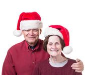Happy Senior Couple in Christmas Santa hats — Stock Photo