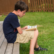 Stock Photo: Boy reading comic books
