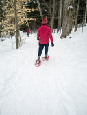 Snowshoeing in winter forest — Stock Photo
