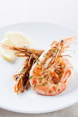 Plate of grilled shrimp with lemon and parsley — Stock Photo