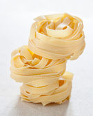 Pile of raw fettuccine nests — Stock Photo