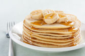 Pancakes with banana and syrup — Stock Photo