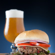 Burger with cheese, onion, tomato and lettuce served with a beer — Stock Photo