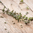Thyme sprigs over wooden table — Stock Photo