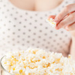 Girl holding a glass bowl of popcorn — Stock Photo