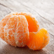 Raw skinned mandarin on wooden table — Stock Photo