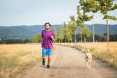 Guy running with a dog — Stock Photo