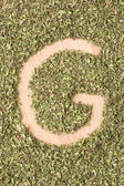 Bokstaven g skrivet med oregano — Stockfoto