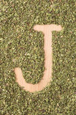 Letter J written with oregano — Stock Photo