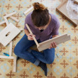 Young woman building piece of furniture — Stock Photo #31946407