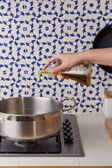 Hand pouring oil on a pan — Stock Photo
