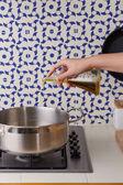 Hand van stromende olie op een pan — Stockfoto