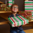 Stock Photo: Smiling boy ready to open Christmas presents