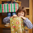 Stock Photo: Girl unwrapping Christmas present