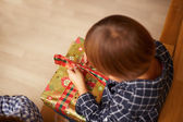 Boy unwrapping a Christmas present — Stock Photo