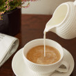 Pouring milk on a coffee cup — Stock Photo