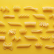 Different types of pasta on yellow background — Stock Photo
