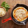 Cooked mozzarella and ham pizza on a skillet — Stock Photo