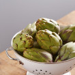 Raw pile of artichokes on colander — Stock Photo