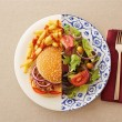 Low fat salad against greasy burger — Stock Photo