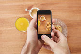 Hands taking photo of breakfast with smartphone — Stock Photo