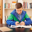 Stock Photo: Teenager texting with smartphone while studying
