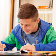 Male confident teenager doing homework — Stok fotoğraf