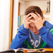 Male teenager worried doing homework — Stock Photo