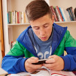 Teenager texting with smartphone while studying — Stock Photo
