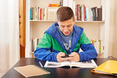 Teenager texting with smartphone while studying — Foto de Stock