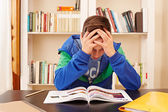 Male teenager worried doing homework — Stock Photo