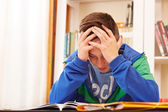 Male teenager worried doing homework — Photo