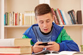Teenager texting with smartphone while studying — Foto Stock