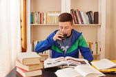 Male teenager drinking coke while studying — Foto Stock