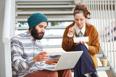 Hipster couple using computer and eating lunch outdoors — Stockfoto