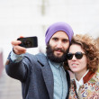 Couple taking a photograph of themselves with a smartphone — ストック写真
