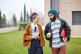 Hipster couple talking and drinking coffee to go — Stock Photo
