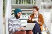 Hipster couple using computer and eating lunch outdoors — Stock Photo