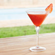 Foto de Stock  : Strawberry daiquiri cocktail by pool outdoors