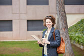 Female redhead student carrying notebook and coffee to go — Stockfoto