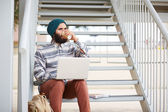 Young bearded hipster student using computer outdoors — Foto Stock