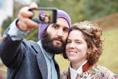 Couple taking a photograph of themselves with a smartphone — Foto de Stock