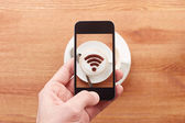 Smartphone taking photograph of free wifi sign on a latte coffe — Stock Photo