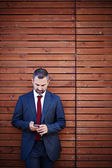 Businessman in a suit with smartphone — Stock Photo