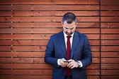 Podnikatel v obleku s smartphone — Stock fotografie