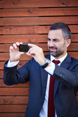 Businessman in a suit taking photograph — Foto Stock