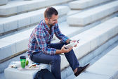 Modern businessman reading outdoors — Stock Photo